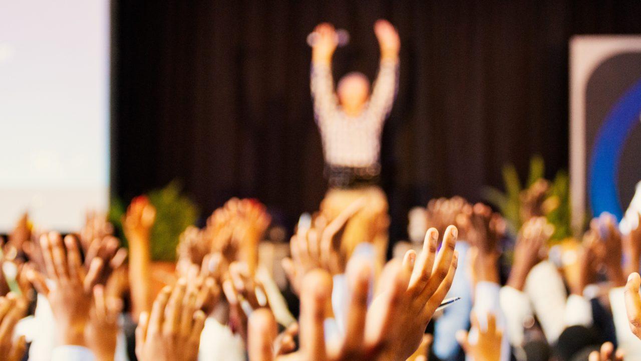 たくさんの人が手を挙げて賛成している様子